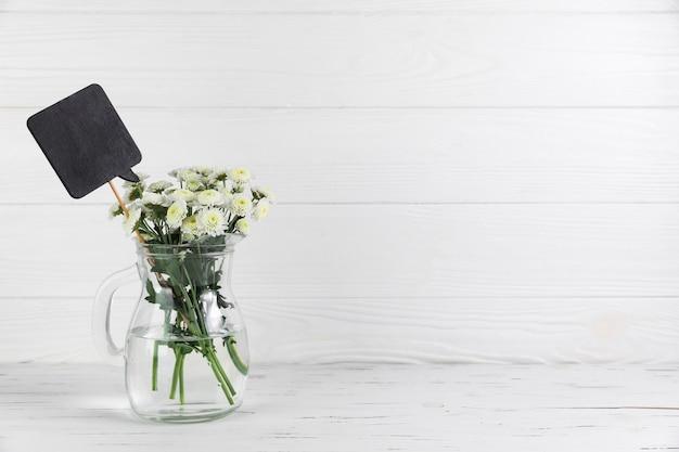 Discurso preto e buquê de flores de crisântemo na jarra de vidro na mesa de madeira branca