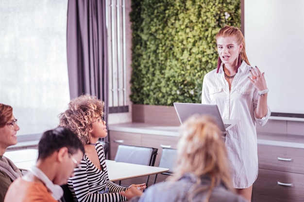 Discussão ativa. menina alegre segurando laptop enquanto fala com seus colegas de grupo