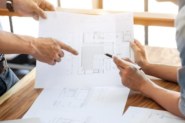 Discussão de dois engenheiros sobre projeto arquitetônico no canteiro de obras no escritório moderno