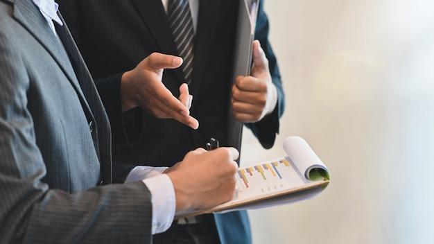 Discussão de empresário colega closeup com relatório de finanças.