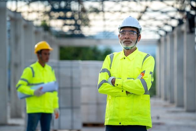 Discussão de engenheiros com arquiteto sobre detalhes de construção no canteiro de obras.