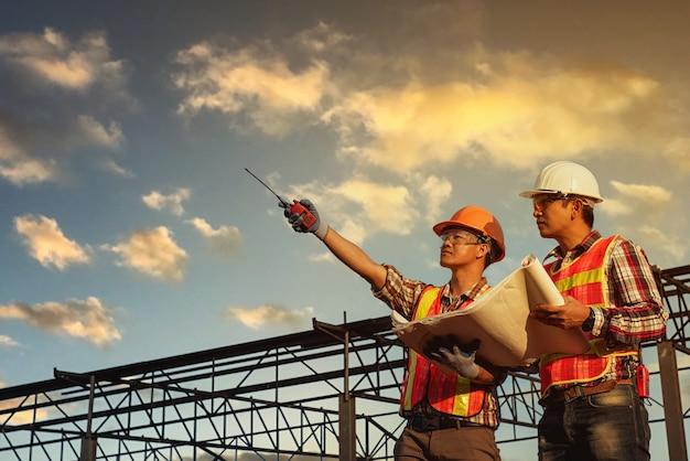 Discussão de engenheiros com arquitetos, planejamento de obras em canteiro de obras
