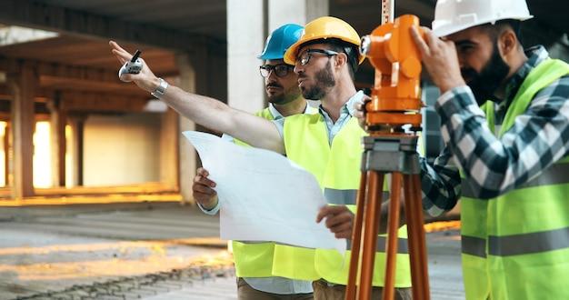 Discussão de engenheiros de construção com arquitetos no canteiro de obras