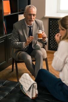 Discussão de especialistas. psicanalista profissional explicando algo para sua paciente enquanto olha para ela