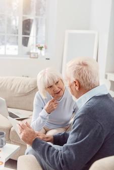 Discussão de intelectuais. agradável casal de idosos sentado na sala de estar, lendo notícias on-line no tablet e falando sobre eventos mundiais