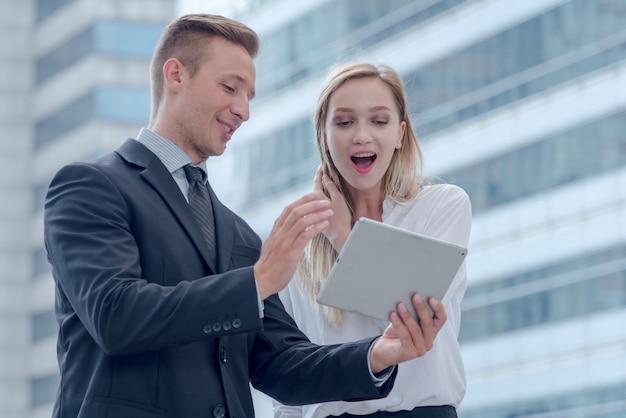 Discussão de negócios sobre trabalho, bolsa de valores e tablet na cidade