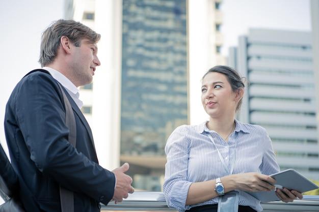 Discussão do homem de negócios e da mulher de negócios no prédio de escritórios exterior.