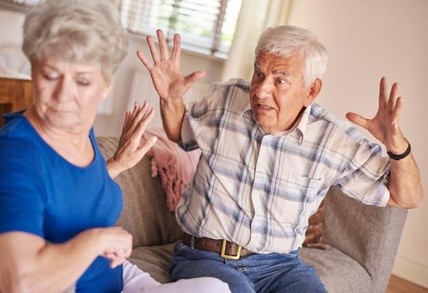 Discussão entre casal de idosos na sala de estar