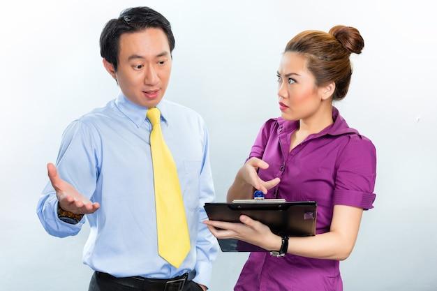 Discussão furiosa entre colegas em um escritório de negócios na ásia