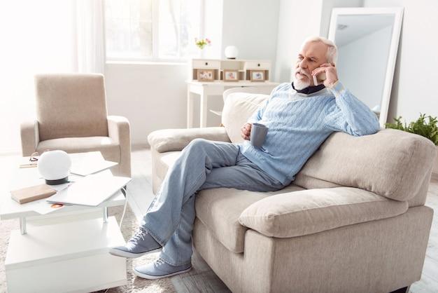Discussão importante. homem simpático sênior sentado no sofá da sala de estar e conversando séria ao telefone enquanto bebe café