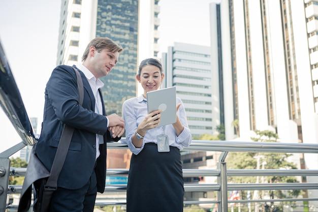 Discussão pela tabuleta do empresário e empresária no prédio de escritórios fora.