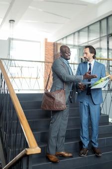 Discutindo a reunião. dois empresários vestindo ternos discutindo a reunião enquanto lêem relatórios