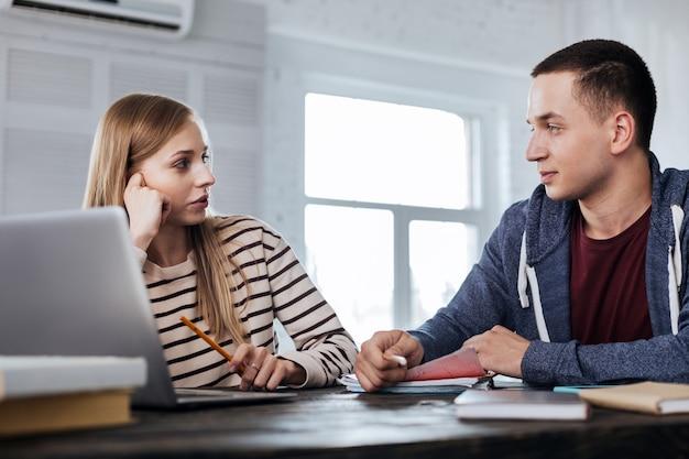 Discutindo. alertar um homem bonito sentado à mesa com seu colega de grupo e discutindo seu projeto
