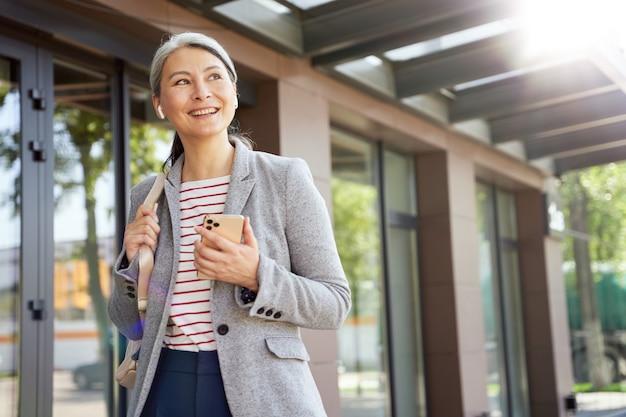 Discutindo negócios. retrato de uma mulher bonita e feliz usando fones de ouvido sem fio usando o smartphone, falando com alguém por telefone em pé ao ar livre. empresários, trabalho