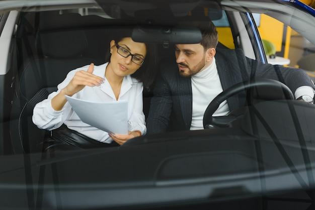 Discutindo novo projeto. dois executivos em roupas clássicas analisando documentos enquanto estão sentados no carro. conceito de negócios. sucesso. parceria