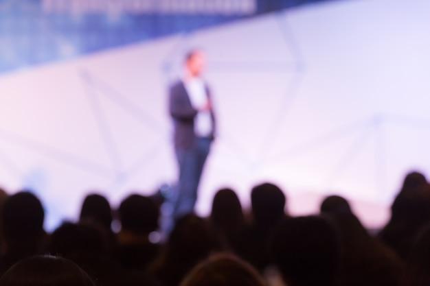 Disfocus do alto-falante falando sobre conferência de negócios.