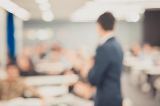 Disfocus do orador dando palestra sobre conferência de negócios corporativos. audiência na sala de conferências. evento de negócios e empreendedorismo.