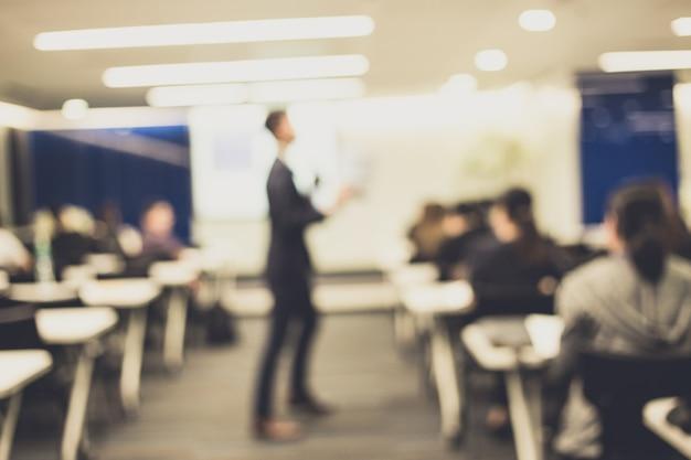 Disfocus do orador dando palestra sobre conferência de negócios corporativos.