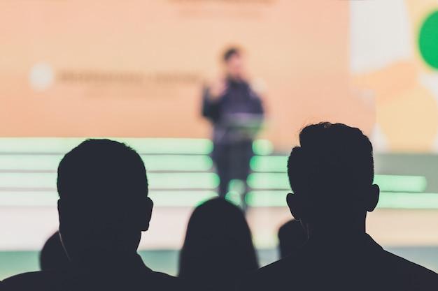 Disfocus do orador no palco e dando palestra em reunião de negócios. audiência na sala de conferências. negócios e empreendedorismo.