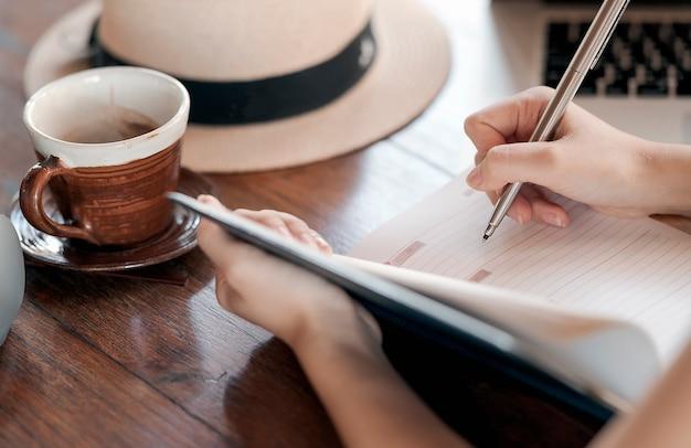 Disparado da escrita fêmea da mão no diário quando relaxe no café com xícara de café.