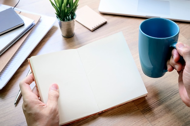 Disparado da mão do homem que guarda o livro com página vazia e a caneca azul ao sentar-se na tabela no escritório.