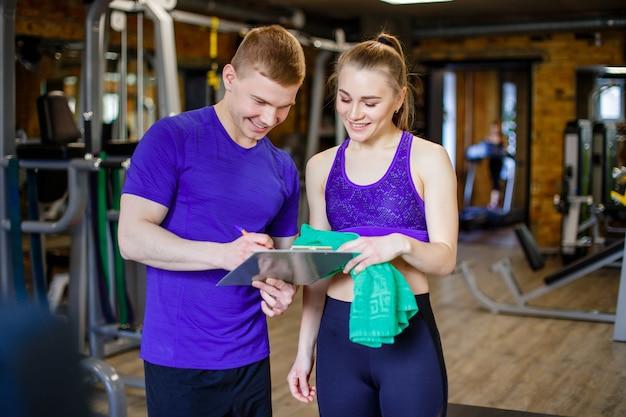 Disparado de um instrutor pessoal que ajuda um membro da ginástica com seu plano de exercício.