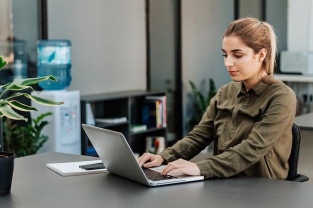 Disparado de uma mulher de negócios criativa nova que trabalha no projeto novo ao sentar-se em seu estúdio na frente do portátil.