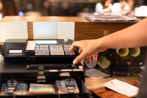 Disparado na mão da luz fraca que pressiona a caixa registadora eletrônica em uma loja.