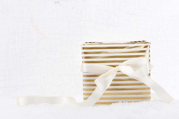 Disparo de caixas de presente brilhantes decoradas com fita deitada na neve branca