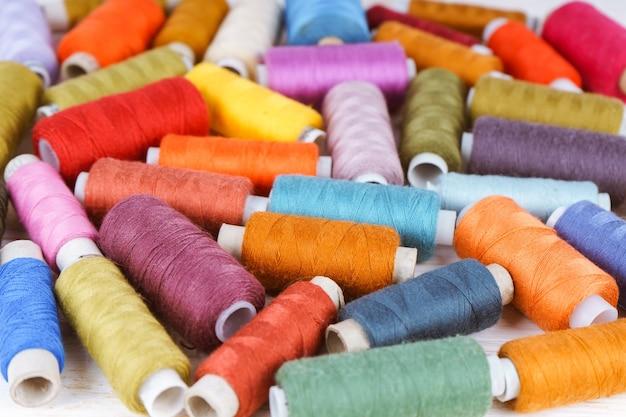 Dispersão de linhas de costura de várias cores na mesa de madeira branca. camada plana, vista superior.