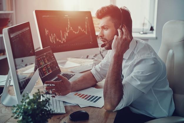 Disponível o dia todo. jovem empresário com fone de ouvido conversando com o cliente enquanto está sentado no escritório