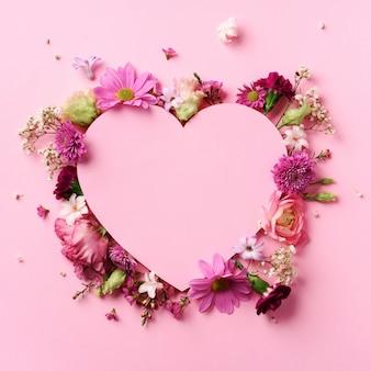 Disposição criativa com flores cor-de-rosa, coração de papel sobre o fundo pastel perfumado. cartão de dia dos namorados. coração de cutted no fundo de papel pastel punchy.