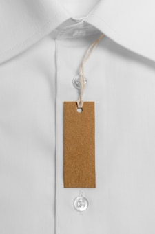 Disposição da vista superior da camisa dobrada com etiqueta de papelão em branco