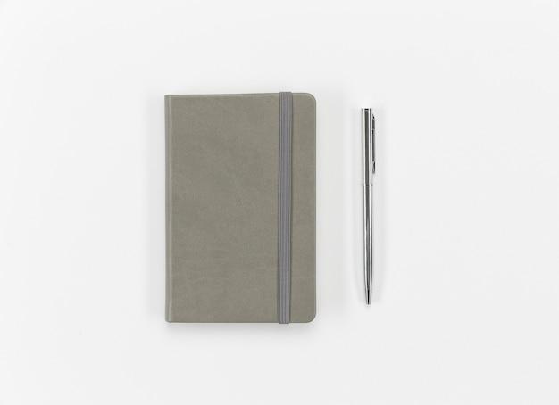 Disposição de caneta e caderno de vista superior