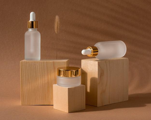 Disposição de conta-gotas de óleo de pele de vista frontal e recipientes de creme facial
