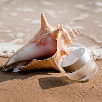 Disposição de recipiente transparente de hidratação para cuidados com a pele ao lado da concha