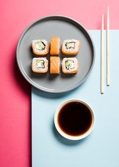 Disposição de rolos de sushi e molho de soja