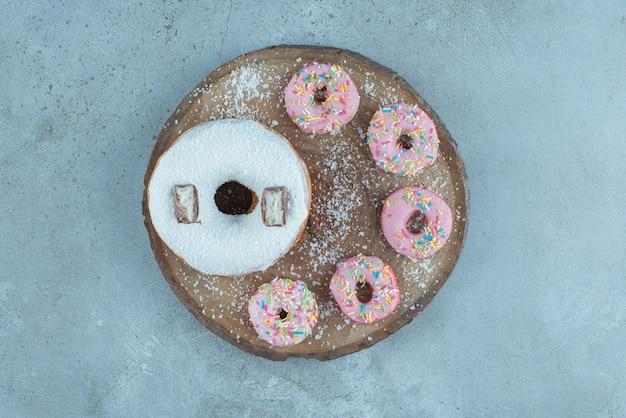 Disposição de um donuts grande e vários pequenos em uma placa de madeira sobre mármore.