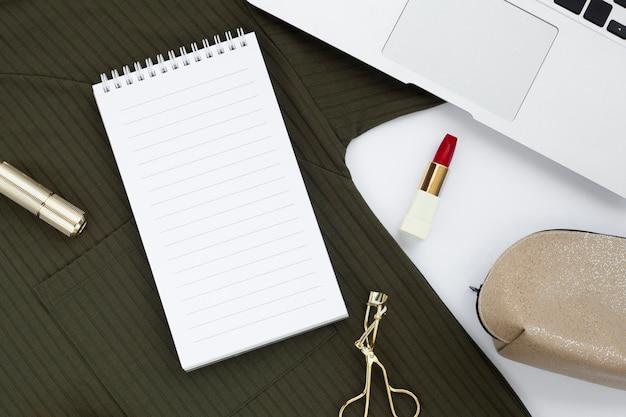Disposição plana com caderno e modelador de cílios