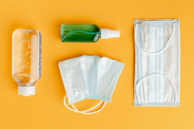 Disposição plana de máscaras médicas com desinfetante para as mãos