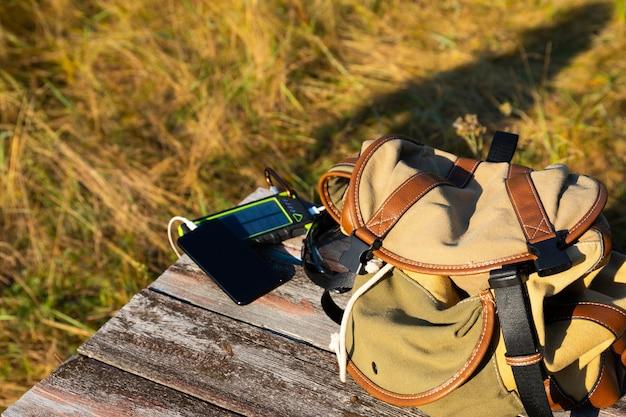 Dispositivo de bateria de energia solar, banco de energia e telefone em uma mesa de madeira com uma mochila. carregue o seu smartphone com energia solar. foco seletivo
