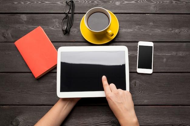Dispositivo de tablet em branco sobre uma mesa de madeira com café