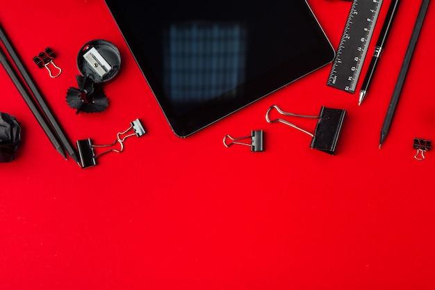 Dispositivo de tela de toque e artigos de papelaria em fundo vermelho