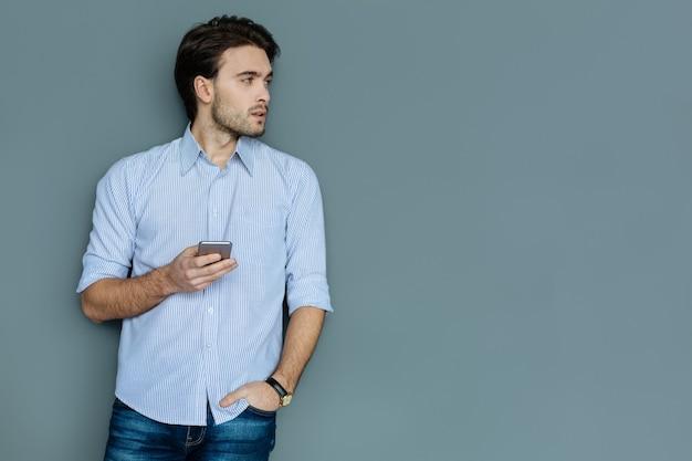 Dispositivo digital. homem inteligente simpático e sério de pé e segurando seu smartphone enquanto olha para o lado