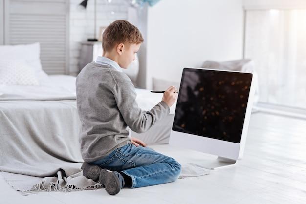 Dispositivo digital. menino inteligente inteligente olhando para a tela e segurando uma caneta stylus e olhando para a tela enquanto está sentado em frente a ela