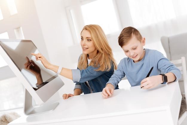 Dispositivo digital. mulher bonita e agradável sentada junto com seu filho e pressionando a tela sensorial enquanto mora na casa inteligente