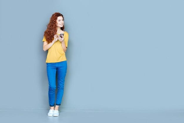 Dispositivo digital. mulher jovem e atraente e alegre em pé contra um fundo azul e sorrindo enquanto usa seu telefone celular