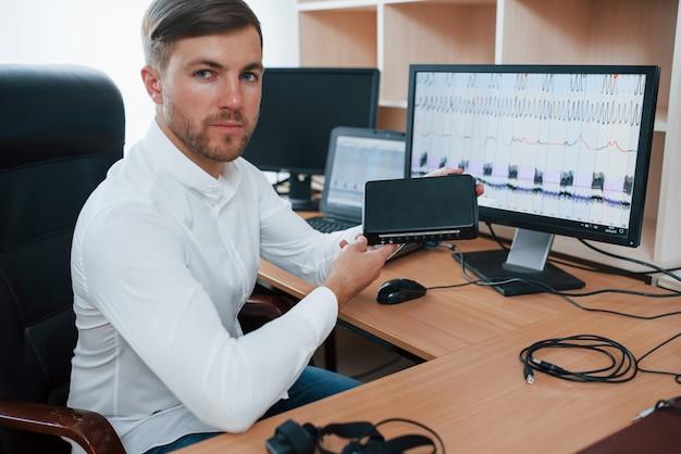 Dispositivo digital. o examinador de polígrafo trabalha no escritório com seu equipamento detector de mentiras