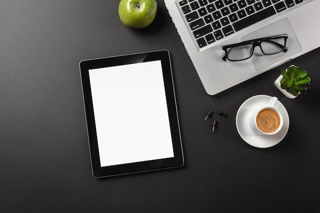 Dispositivo do tablet pc na mesa do homem de negócios e no copo de café. vista superior com espaço para texto