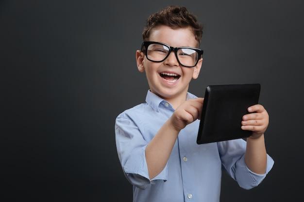 Dispositivo educativo. menino inteligente e diligente usando seu tablet e parecendo animado enquanto encontra algo interessante